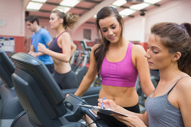 Female gym instructor and smiling woman in the gym on the treadmill
